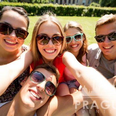Five young people with sunglasses taking a selfie in the summer