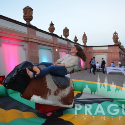 Young girl riding mechanical bull at Troja Chateau Garden