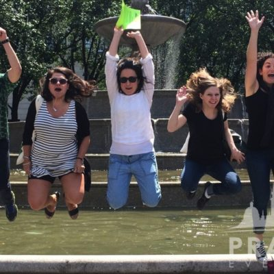 Multiracial group of people jumping in front of fountain